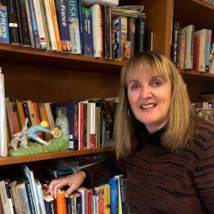 Image of Julie Faulkner with shelf of books.