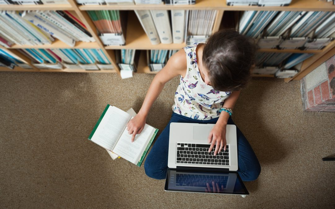 Student working on floor in library with laptop and books.